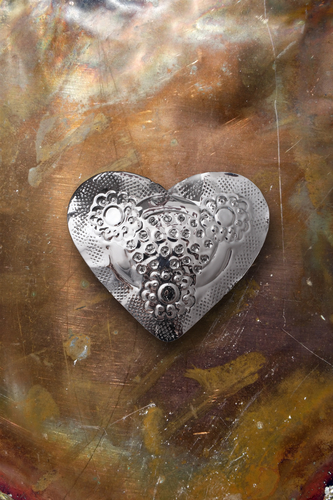 Chrome metal heart on tarnished copper