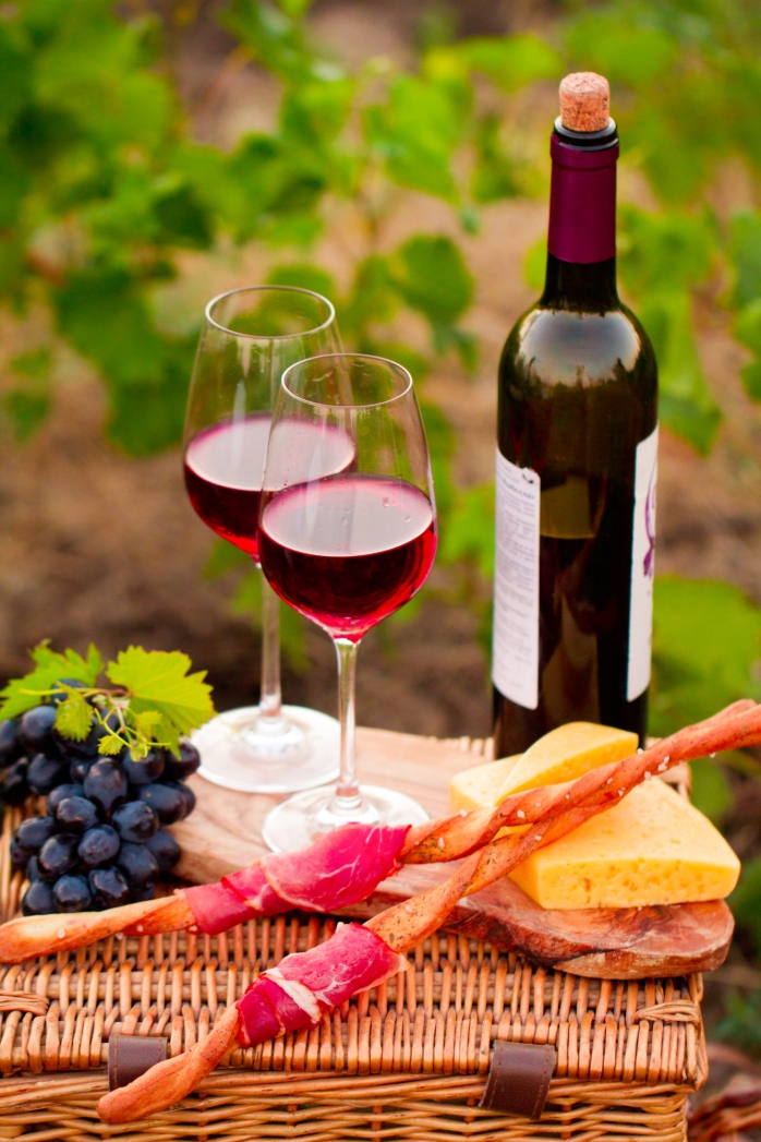 Two glasses of red wine with bottle,  bread, meat, grape and che